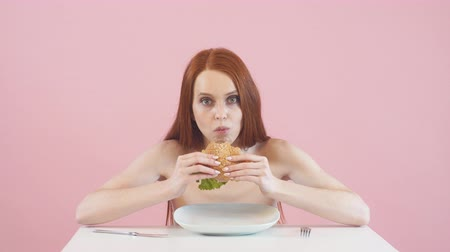 eredmények : Happy anorexic girl greedily eating a Burger. Violation of diet. Anorexia. Stock mozgókép
