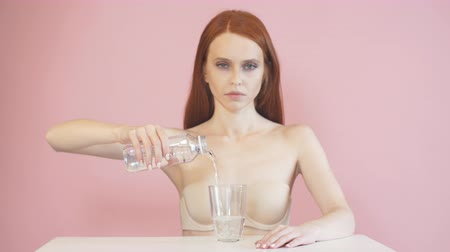 cuidados com a pele : Exhausted red-haired girl pours water into a glass. Diet. Anorexia.