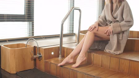 bathhouse : Young beautiful blond woman sitting on edge of wooden tub with a warm water, placed near the big panoramic window in finnish sauna Stock Footage