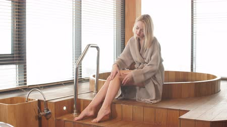 stayed : Long -legged blonde young female tourist enjoying peaceful and still atmosphere in spa centre of luxury hotel, where she stayed, sitting near wooden round tub against big windows