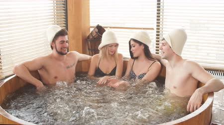 banheira : Group of male and female friends visiting bathhouse in holidays, being overjoyed and happy, enjoying jacuzzi in hot wooden round barrel Stock Footage
