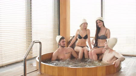 джакузи : Two loving couple enjoying hot wooden whirlpool with warm water in modern bathhouse of a luxury hotel