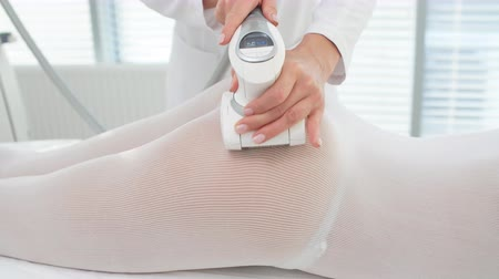 legs only : Young brunette female therapist doing beauty therapy against cellulite with LPG machine on woman buttocks in health and wellness medical clinic. LPG massage for lifting body