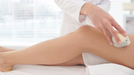 legs only : RF lifting massage, Close up of cosmetologist doctor hands manipulating with hardware cosmetological gadget. Slender body shaping.