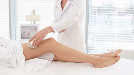 legs only : Female cosmetologist doing Rf lifting procedure on womens long slim legs in a beauty parlor. Treatment of overweight and flabby skin.