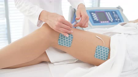 oturum : Beautician hands operating with Electric device, sticking electrodes to female hips. Myostimulation session performed on the slim female legs with healthy skin