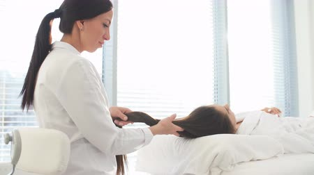 revitalizing : Facial spa cosmetology procedure. Skin care lift anti age massage. Caucasian brunette woman dressed in white bathrobe, receiving anti-wrinkle and skin rejuvenation treatment at beauty salon.