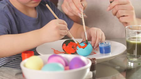 easter : Easter concept. Happy mother and her cute child getting ready for Easter by painting the eggs.