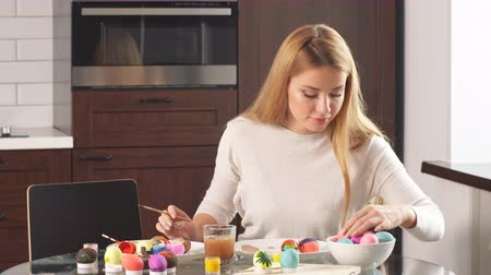 húsvéti tojás : Family prepares for holiday. Easter and happy moments concept. Woman and little boy with smiling faces making decorations. Mother and son painting eggs for Easter.