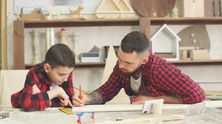 statuette : Dad showing video on laptop to his son before working with wood together, standing in the carpenter s workshop surrounded with tools and wooden figures