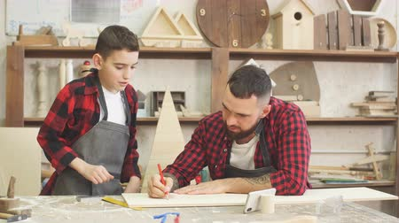 statuette : Dad and son looking at smart phone together while choosing a model for creating a family masterpiece standing in the carpenter s workshop surrounded with tools ans wooden figures.