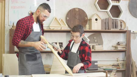 dýka : Father and little son testing hand-made wood sword evenness at workshop. Dostupné videozáznamy