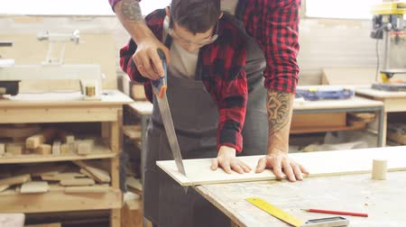 otcovství : Dad and his son are working in the workshop. They are sawing wooden planks.