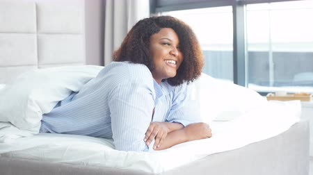darkskinned : Beautiful awesome woman has joyful expression, lies on stomach in bed. Emotion, feeling, happiness Stock Footage