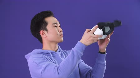 újító : Korean young man surprised by something in virtual reality, wearing virtual reality glasses showing gesture isolated on studio shot on violet wall background