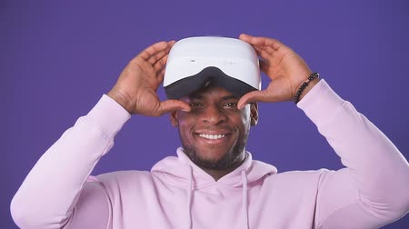 algılayıcı : African handsome man wearing a sports hoodie wearing a VR headset from his head, impressed by the virtual effects, smiling happily on a purple purple background