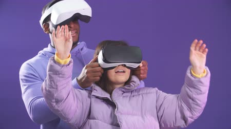 感動 : Young interracial couple having first experience of using virtual reality headset, standing joyful and impressed in studio with violet background