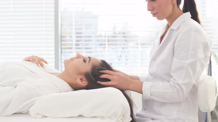 revitalizing : Beautician doing head massage or prepare female patient to hardware cosmetology procedures. Beauty concept. Cosmetology concept. Cosmetology salon.