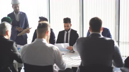 tudo : Male caucasian employee presents business strategy on white paper shift to top managers of his company in boardroom. Chief is standing beside, all the others, in formal wear are sitting