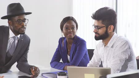 magyarázza : African corporate business coach explains basic principles of corporate strategy to diverse mixed-race employees at their first meeting at conference room.