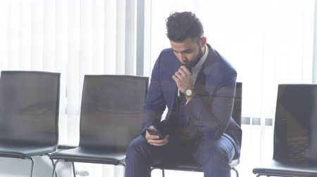 rekrutacja : lonely handsome man in fashion suit sitting with smartphone.