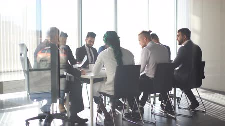 affiliate : Multiracial team of business partners of different age interacting in boardroom of modern spacious and well-lit office, being viewed through transparent glass wall.