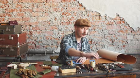 elegancia : young hardworking guy working with leather using crafting tools at workshop. lifestyle, hobby