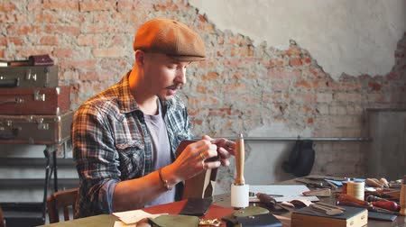 striker : Man in checked shirt sewing leather item for customers. Creative work