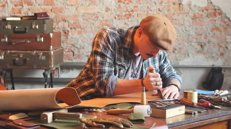 шить : Handsome young shoemaker, wearing a shirt and a cap, cutting leather in workshop with special knife