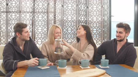 bathhouse : Cheerful young male and female friends in soft bathrobes sitting at table with cups ,chilling in spa after massage procedure Stock Footage