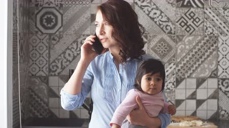 baby infant : Busy serious mother holding her baby and talking on the smartphone in the kitchen.