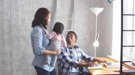 支出 : Young multi-ethnic parents smiling while spending time with their sweet little baby. 動画素材