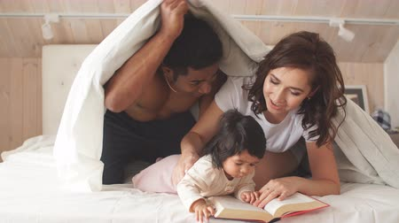 物語 : Happy parents reading a book to cheerful child while covering with a blanket. Lifestyle, interest