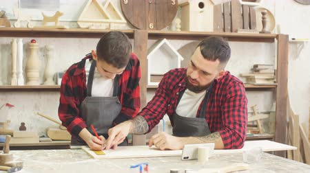 oyma : Dad showing video on laptop to his son before working with wood together, standing in the carpenter s workshop surrounded with tools and wooden figures