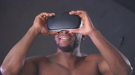 感動 : African handsome man wearing a sports hoodie wearing a VR headset from his head, impressed by the virtual effects, smiling happily on a purple purple background