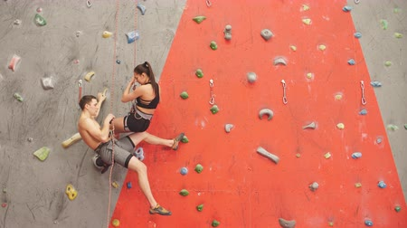 coordinatie : Young positive man and a beautiful woman making friends at the climbing center. Couple having fun in the sport club