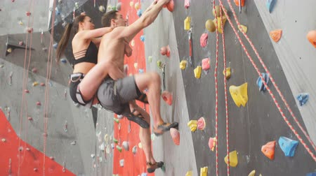 wspinaczka : Young awesome couple doing aerobic exercise at climbing gym. Climbing technique, difficulties in climbing