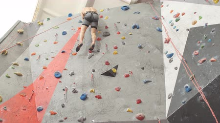 bouldering : Free ambitious young man climbing on artificial wall. Guy reaching the top of mountain Stock Footage