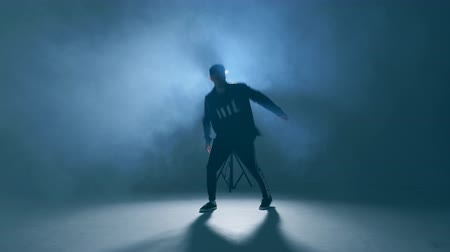 chmiel : Sporty modern style hip-hop dancer dressed in urban style wear shows his dance on blue studio background.