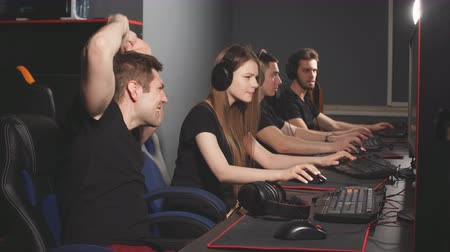 walkthrough : Team of gamers in headphones emotionally rejoices in victory playing in e-sport club, looks at the computer screen and enjoying their triumph. Stock Footage