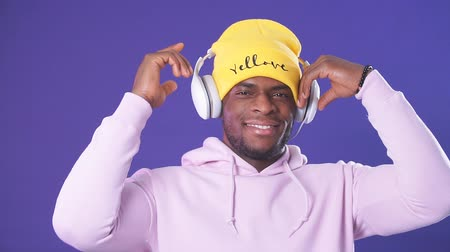 içerik : Happy surprised dark-skinned guy in hoodie and yellow hat listening to favorite tracks in headphones