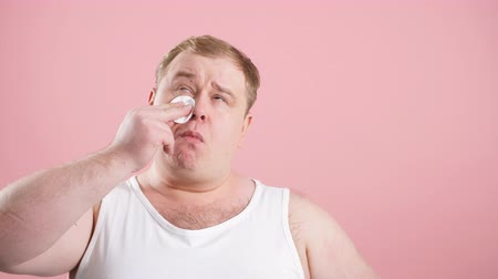 nevetséges : Funny glad jouful man in undershirt applying tonic by cotton pad on face isolated on pink studio background. Hygiene concept, cosmetical goods for skin care