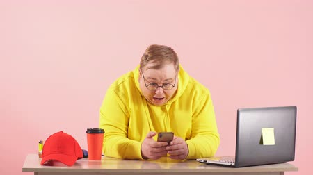 head over : Shocked surprised plump man in yellow sportswear staring at camera with open mouth while working on smartphone over pink background