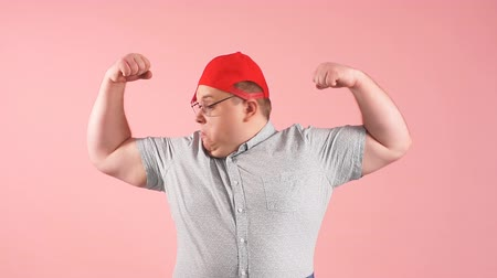 nevetséges : Funny comic overweight man dressed in casual wear shows his muscles with confident expression, aims at promoting sports participation and healthy lifestyle