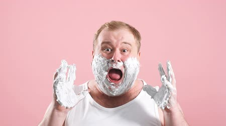 undershirt : Young shocked astonished man standing in white underwear isolated over pink background with shaving foam on face. Looking at camera, slow motion. Stock Footage