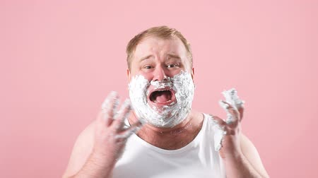 shaving foam : Upset man with gel on cheeks, has sad expression, sensitive skin, man going to shave his chin despite ofskin irritation, isolated over pink background.