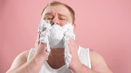 undershirt : Astonished surprised man stares at camera, has shaving foam on face, dressed in white underwear, feeling impressed by new shaving gel, isolated over pink background. Grooming concept.
