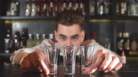 autêntico : Smiling happy bartender puts the shot glass for vodka.