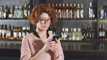 coppery : Red-haired woman using smartphone in restaurant standing near bar stand with shelves of alcohol Stock Footage