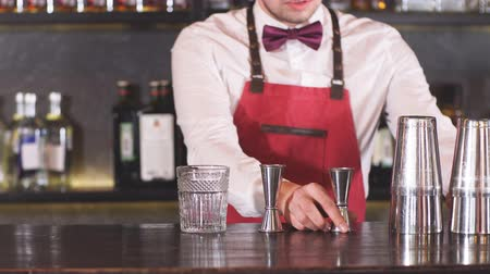 migalhas : Bartender in the white shirt and red apron adding ice crumbs into an empty cocktail glass on the bar counter at restaurant
